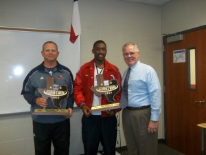 Chuck Kramer, GM/OP (right), presents Ford's awards to Greg Campbell and Coach Craig Stump.