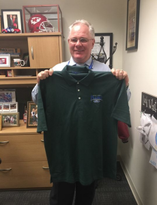 Chuck Kramer, GM/OP, shows his Project Green Light shirt off that the team is wearing this Veterans Day.
